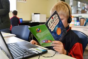 boy reading and using laptop